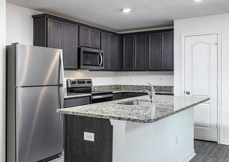 Full kitchen with installed appliances, granite countertops and upper-wood cabinets with crown molding.