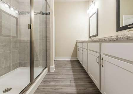 Full bathroom with a large standing shower and double sinks with granite countertops.
