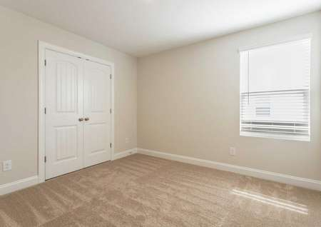 Avery bedroom with tan carpets, white French doors, and large window