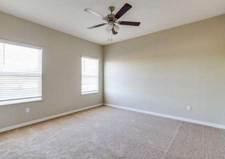 The master bedroom in the Mykka floor plan that has light brown carpet, tan walls, a ceiling light fan and two windows.