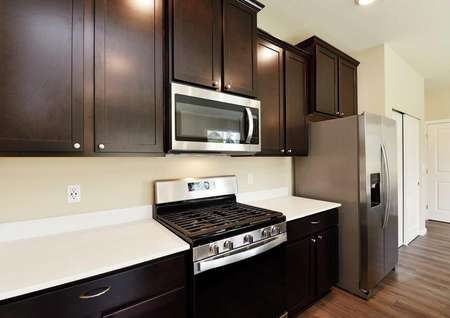 The Northwest Chelan side view of the kitchen shows white quartz countertop and dark brown cabinets.