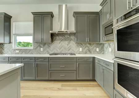 The kitchen has a double oven, gas cooktop and is accented by a beautiful backsplash.