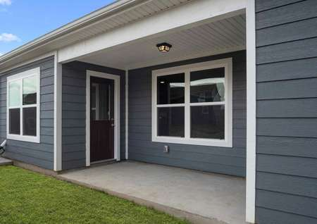 The Blanco model homes view of the back patio with large window and door with grey siding and manicured back lawn