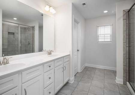 Fripp master bath with tile floors, walk-in shower, and dual sink vanity with large mirror