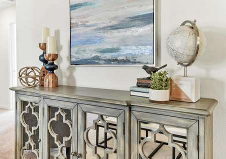 Walnut model home with a seascape painting on the wall plus a globe, books, and candles sitting on a decorative wooden credenza with mirrored doors