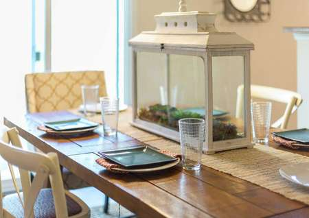 The Madison model home staged dining room with wooden table and chairs, place settings with plates and glasses, and a white glass framed box centerpiece