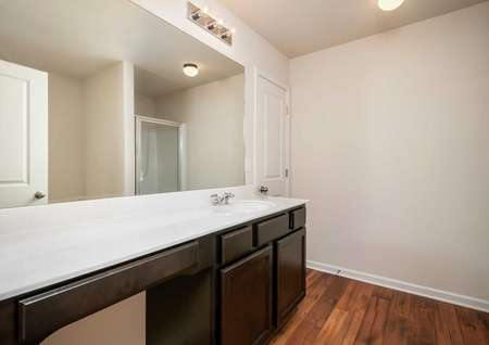 Hartwell bathroom with wood flooring, brown cabinets with white top, and wall light fixture
