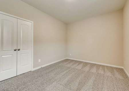 Secondary bedroom with tan walls, white trim and brown carpet.