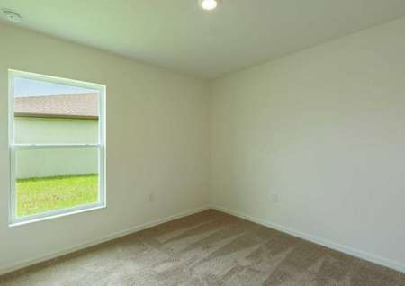Carpeted spare room of the Estero floor plan witha single hung window, carpet and a light fixture on the ceiling.