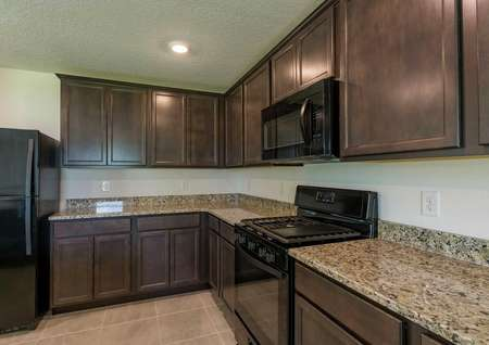 Cocoa plan's kitchen with granite countertops, brown cabinets, tile flooring and all black appliances.