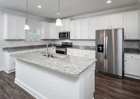 Kiawah plan's kitchen with granite countertops, white cabinets, stainless steel appliances& an island that has a sink.