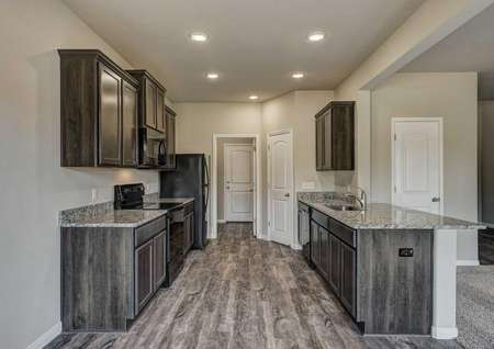 Cypress kitchen with recessed lights, wood floors, and brown cabinets