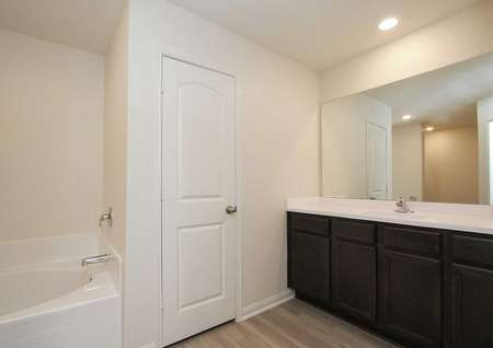 Master bath with cultured marble counters, vinyl wood-style flooring, and dark brown cabinetry in the Rayburn floor plan