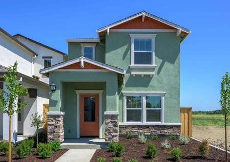 The exterior of theCrystal floor plan's two-story model with a decorative front door and a beautifully landscaped front yard.