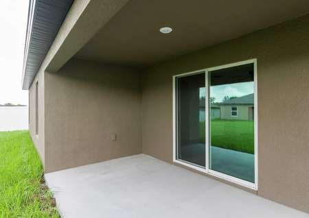 Shaded back patio with sliding doors for plenty of entertainment space.