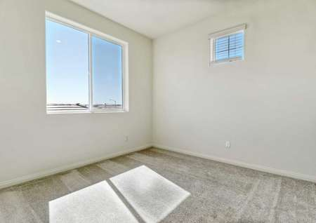 A bedroom with carpet flooring, two windows and white walls in the Sunflower floor plan.