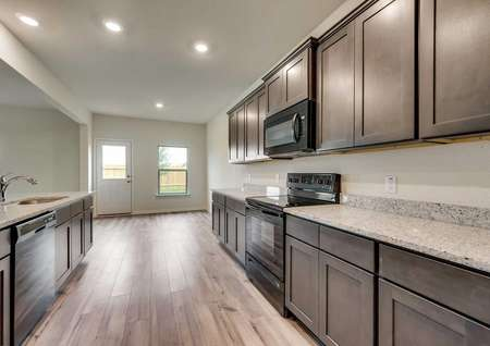 Oakmont kitchen with vinyl flooring and dark brown custom cabinets, black appliances and recessed lighting