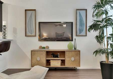 Staged living room photo with a tv mounted on the wall above a wooden entertainment system with two doors and a tall green house plant.