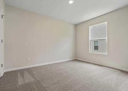 Allatoona bedroom with can lights, cream walls with white trim, and brown carpets