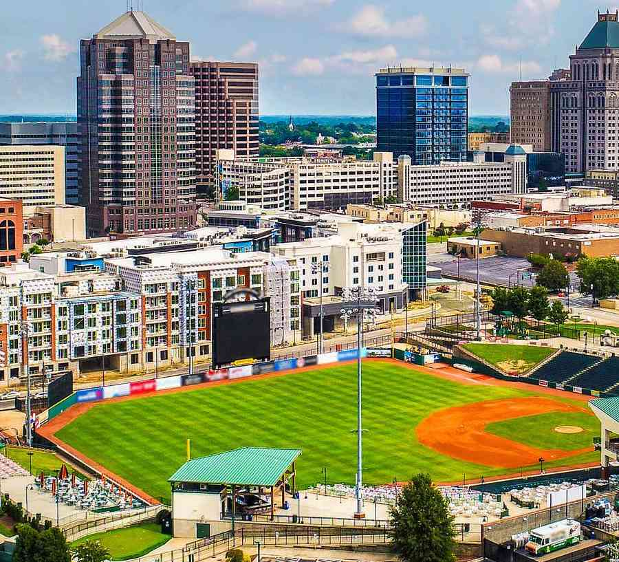 Downtown Greensboro, North Carolina cityscape photo taken from the sky showing skyscrapers, sports grounds, and apartment buildings