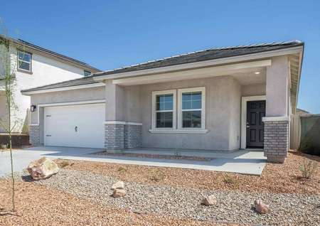 Laguna finished single-family home with 2 car carriage style garage door, desert landscaping, and gray siding