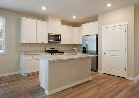 The kitchen comes complete with stainless steel appliances and white cabinetry.