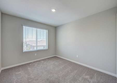 A spare bedroom upstairs in the Loomis floor plan with carpet floors, a large window and a ceiling light fixture.