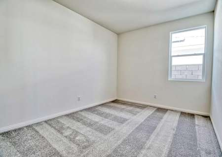 A spare bedroom in the Rosebud floor plan with awindow, carpet flooring and multiple wall outlets.