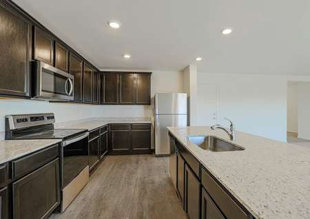 Incredible designer kitchen with stainless steel appliances, granite countertops, espresso cabinets and a kitchen island with an undermount sink.
