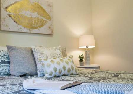 Staged bedroom with painting that has golden lips, bed with multiple pillows and blue comforter and light in the corner.