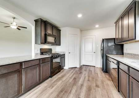 Whichita kitchen completed with overhead lights, abundant cabinets, and black modern appliances