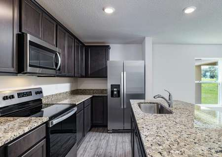 Chef-ready kitchen features granite countertops, upper-wood cabinets and stainless steel appliances.