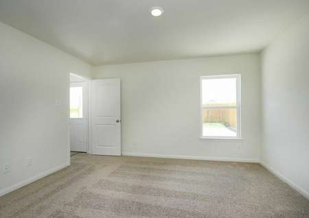 Trinity bedroom with white doors and baseboards, brown carpet, and white framed window