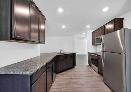 Long, granite countertops in a kitchen that also features brand-new stainless steel appliances.