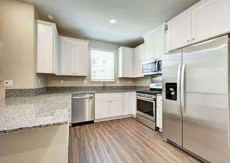 The kitchen withwhite wooden cabinets, granite countertops and all stainless steelappliances in the Kennedy floor plan.