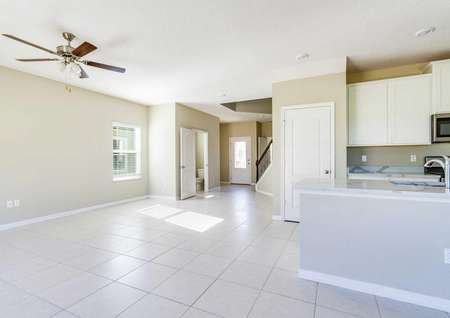 Wide view of the the kitchen and the living room that has tile flooroingfrom the dining area in the Tomoka floor plan.