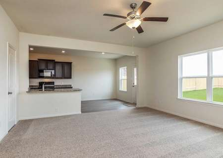 Cypress great room with light-colored carpets, hardwood flooring in the kitchen and dining area, and overhead ceiling fan