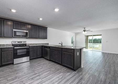 Chef-ready kitchen overlooking entertainment space with large windows.