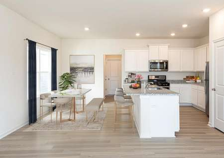 Spacious, open kitchen and dining room with pale plank flooring, kitchen white cabinets, gray granite, barstools at island, rectangle dining table with 4 chairs and a bench, window with drapes and recessed lighting.