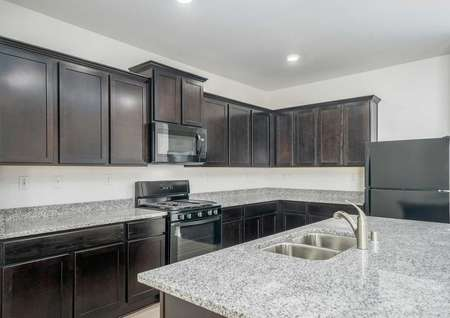 Redondo kitchen with light grey counters, custom brown cabinets, and black stove / oven