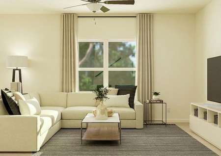 Rendering of the living room focused on a   large window. The room has a ceiling fan and carpeted flooring and is   decorated with a cream sectional couch, wood coffee table and entertainment   center.