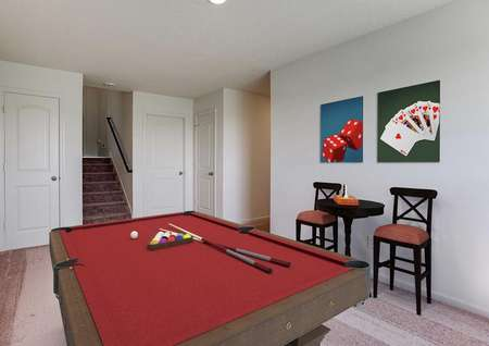 Staged game room with red-felt pool table that has set of balls and two cues on it, two game-themed pictures on the wall, and two wooden barstools on either side of a bar table.