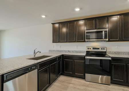 Incredible chef-ready kitchen filled with stainless steel appliances, sprawling wrap-around granite countertops and an undermount sink.