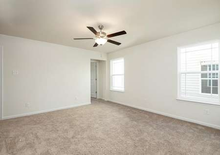Spacious upstairs game room with ceiling fan and two windows and closet, view to hallway