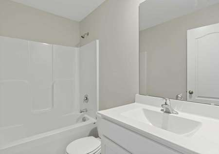 Burton white on white bathroom with modern fixtures, tub/shower combo, and large vanity mirror
