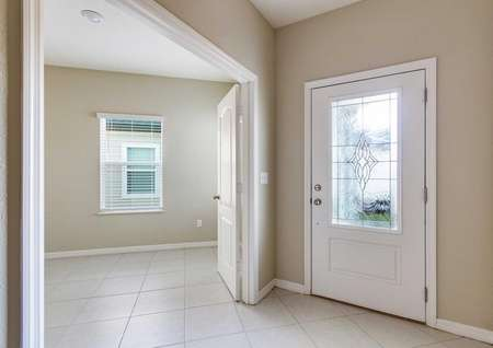 The tile-floored hallway in the Mykka floor plan that leads to the decorative white front door with glass.
