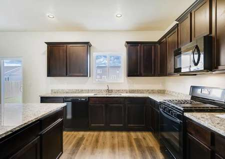 Mesa Verde kitchen with wood cabinets, tile floors, and black appliances