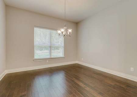 Fairview dining room with 5 lamp chandelier, hardwood brown floors, and white baseboards on gray painted walls