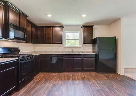 Aitkin kitchen with black appliances, dark wood cabinets, and granite countertops