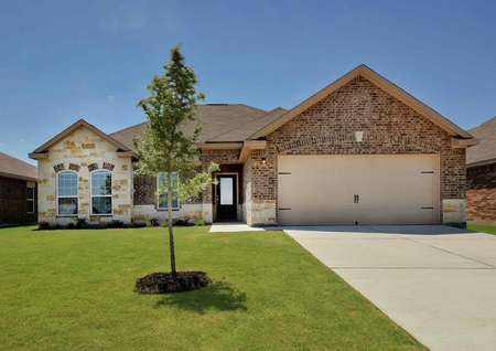 One-story Hendrie plan by LGI Homes with brick and stone exterior, glass front door, landscaped front yard.